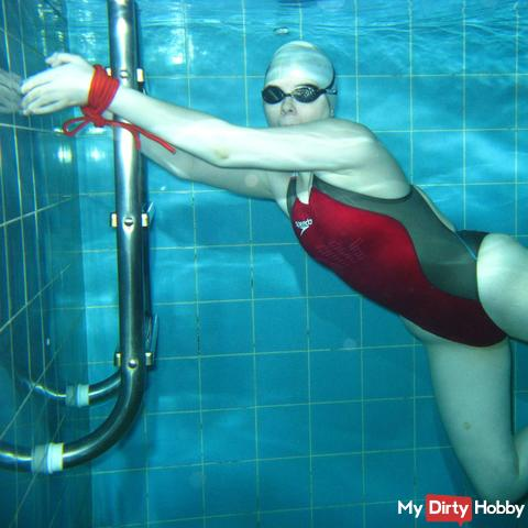 Gagged and bound underwater in red Fastskin suit
