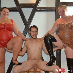 Naked man fingering two women in lingerie 1